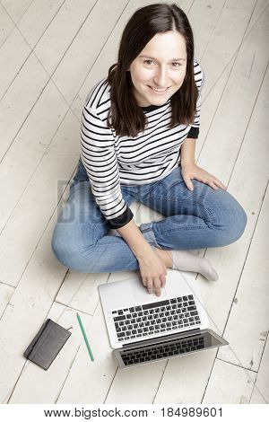 Beautiful young happy woman working with a laptop sitting on a white wooden floor lying next to a notebook and pencil