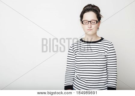 Calm attractive young woman with closed eyes in glasses and a striped sweater standing on a white background