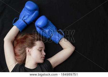 A girl in boxing gloves lies on the floor with her eyes closed in a knockout