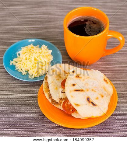 Traditional delicious arepas, shredded chicken avocado and cheddar cheese and shredded beef with a cup of coffe with grated cheese in bowl on wooden background.