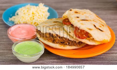 Traditional delicious arepas, shredded chicken avocado and cheddar cheese and shredded beef with grated cheese, avocado and pink sauce in bowl on wooden background.
