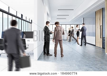 People are walking in an open office interior with panoramic windows white walls computer monitors on desks and a reception counter in the lobby. 3d rendering mock up