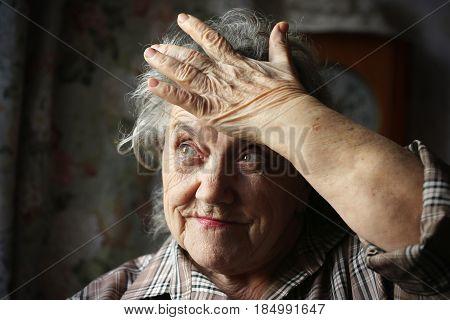 Elderly woman stress and headache on a dark background