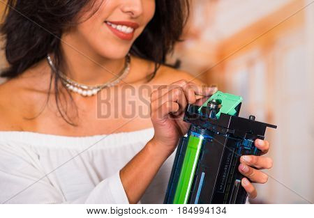 Closeup of a beautiful woman fixing a photocopier and smiling during maintenance repairs using handheld tool.
