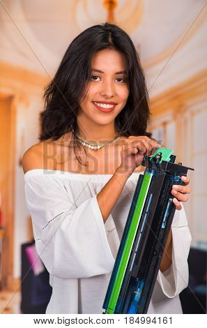 Beautiful woman fixing a photocopier and smiling during maintenance.