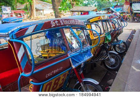 Bacong Philippines - 26 June 2016: Tricycle - public form of transport in the Philippines. Tuk-tuk or rickshaw colorful motorcycle with handmade passenger seat. Personal vehicle with three wheels