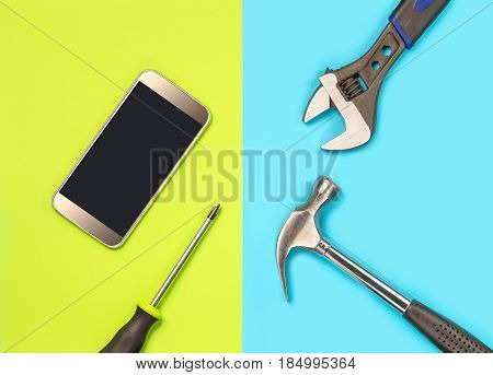 Smartphone repair concept for cellphone fixing company's marketing. Fix broken telephones and solve virus spyware problems. Cellphone and tools on colorful vibrant light green and blue background.