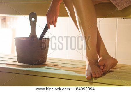 Woman in sauna holding ladle about to throw water from the bucket to the stove. Girl enjoying the hot air and sitting legs and feet crossed on the wooden bench. Traditional relaxation in Finland.