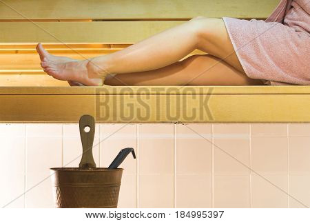 Long legs resting on wooden bench in authentic Finnish city sauna. Young woman enjoying hot relaxation wearing a pink towel. Healthy lifestyle concept.