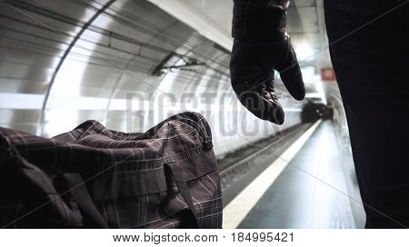 Bomber standing next to his black bomb bag planning a strike. Terrorist in underground subway tunnel looking at the empty metro platform. Security threat in public transportation. Terrorism concept.