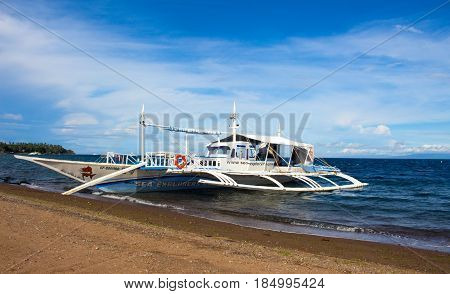 Dauin Philippines - 1 March 2017: Boat near the beach. White wooden catamaran in blue sea. Traveling tropical island. Sea and sky landscape. Sunny exotic seashore. Traditional Filipino boat bangka