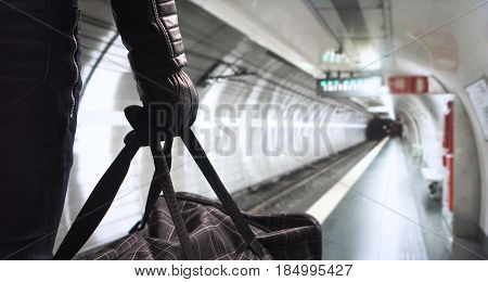 Terrorism in subway concept. Dangerous criminal with black bomb bag standing in underground station planning attack. Threatening man in the shadow with an evil plan . Terrorist in metro platform.