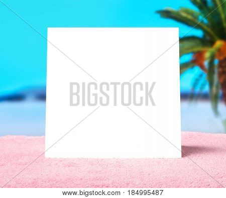 Spring offer or summer sale template background. White blank square card with free copy space on a towel on beach with beautiful blurred paradise ocean background. Hot vacation and holiday feeling.