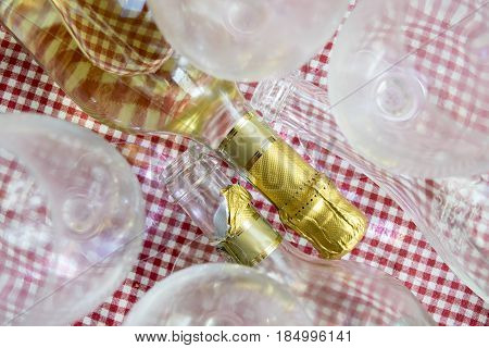 full and empty bottles of white wine lying down between champagne flute