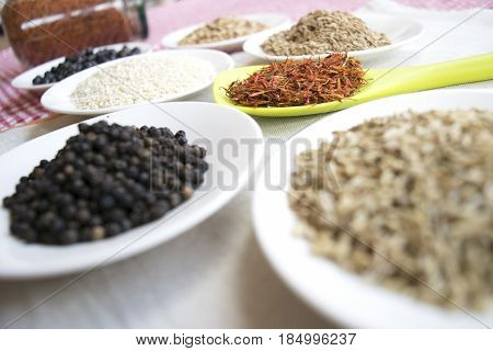 assortment of spices with saffron in pistils on a colored ladle