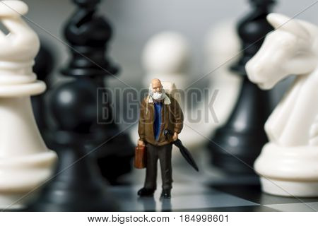 Miniature doll traveler and chess. Old traveler in chessboard. Senior traveller with suitcase. White and black chess figurines. Model learning to play chessmate. Big figures and small man concept