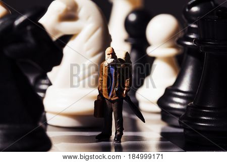 Retro traveler and chess figures on board. Old traveler in chessboard. Senior traveller with suitcase. White and black chess figurines. Model learning to play chessmate. Big figures and small man