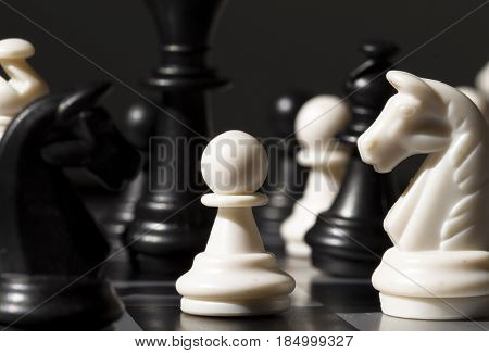 White pawn between black figures on chessboard. Checkmate game process. Black queen and Knight over white pawn. Business strategy advantage concept. Tactic threat in tablegame. Smart table game photo