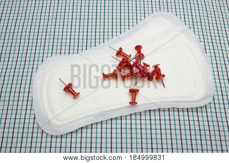 Red sharp office pins and clean menstruation cotton sanitary daily pad on the plaid blanket. Photo for woman hygiene protection. Soft tender protection woman critical days menstruation cycle