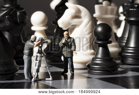 Chess news making. Filming chess game process. Miniature journalists on chessboard. Chess game in process broadcast. Chess playing story. Chessmate reporters brief scene. Black and white figures