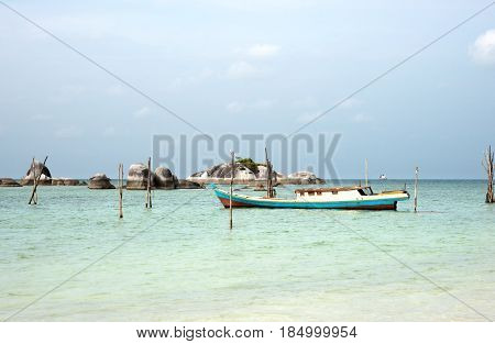 Empty Fishing Boat Docked At The Turquoise Colored Ocean Coast Near White Sand Beach In The Afternoo