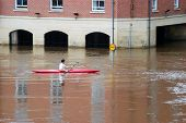 Male canoeist takes advantage of the flooded River Ouse in York. poster