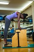 Determined woman exercising on wunda chair in gym poster