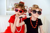 Two funny little girls with curlers in their hair make themselves a make-up. Kid's fashion. Family at home. poster