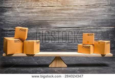 Two Piles Of Boxes On The Scales. Trade Balance And Calculation By Barter. Bypassing Sanctions, Impo
