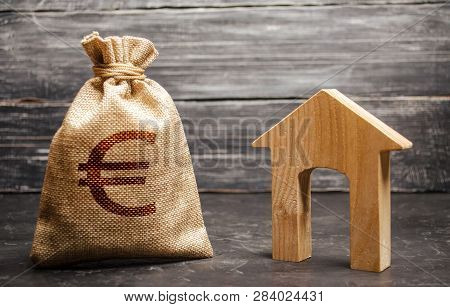 A Bag With Euro Money And A House With A Large Doorway. Taxes, Rental Income. Building Houses. Rent
