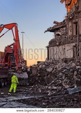 Unidentifiable Man In High Visibility Clothing Working In Front Of An Orange Excavator On The Demoli