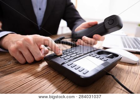 Person's Hand Dialing Telephone Number To Make Phone Call