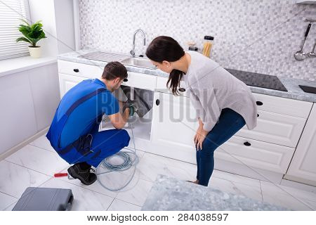 Woman Looking At Male Plumber Cleaning Clogged Sink Pipe With Drained Cable In Kitchen