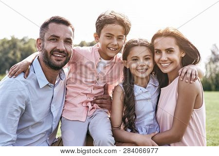 Bonding. Family Of Four Standing On A Grassy Field Hugging Looki