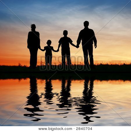 Family Of Four On Sunset Sky Water