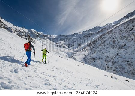 Couple Of Friends Uphill With Skis And Seal Skins.