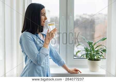 Young Woman Morning At Home Near The Window Drinking Water With Lemon, Vitamin Drink In Winter Sprin