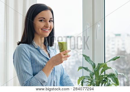 Young Woman Morning At Home Near The Window Drinking Freshly Blended Green Kiwi Fruit Smoothie In Gl