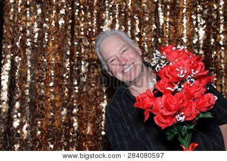 Man in a Photo Booth. A Caucasian man smiles and has fun posing in a Photo Booth with a Gold Sequin curtain. White male with red roses looks into the camera and smiles.