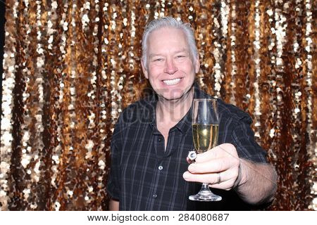 Man in a Photo Booth. A Caucasian man smiles and has fun posing in a Photo Booth with a Gold Sequin curtain. White male drinks and toast a Champagne Glass into the camera and smiles.