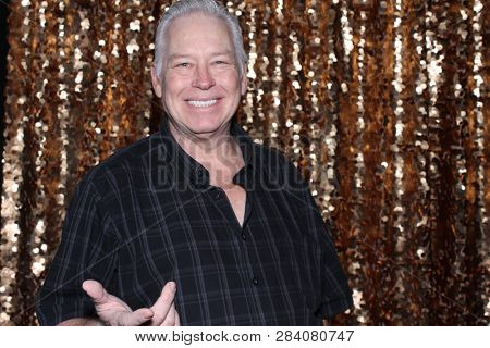 Man in a Photo Booth. A Caucasian man smiles and has fun posing in a Photo Booth with a Gold Sequin curtain.