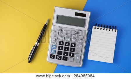 Calculator On Vivid Yellow And Blue Background