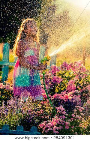 Summer fun, watering flowers - lovely girl has fun watering flowers in the garden