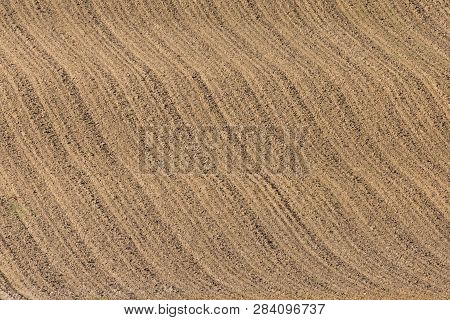 newly furrowed brown farmland with symmetrical furrows poster
