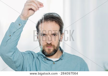 serious bearded male hypnotist holding dowsing and looking at camera poster
