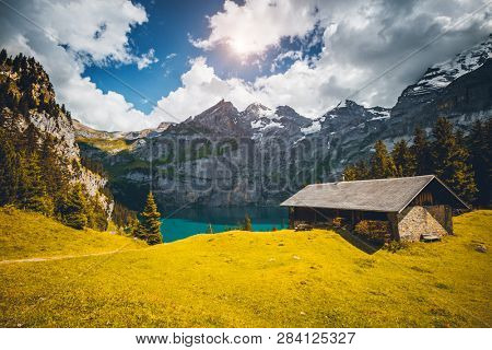 Idyllic panorama view of the lake Oeschinensee in day. Location place Swiss alps, Kandersteg, Bernese Oberland, Europe. Scenic image of most popular tourist attraction. Discover the beauty of earth.