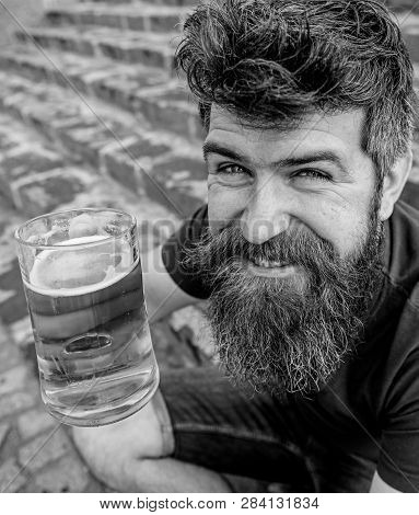Guy having rest with draught beer. Hipster on cheerful smiling face drinks beer outdoor. Celebration concept. Man with beard and mustache holds glass with beer while sits on stone stairs, defocused poster