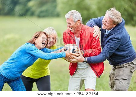 Group of seniors is having fun while racking and playing with a football in the park