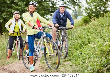Active senior group makes a bike tour in nature as a cycling holiday