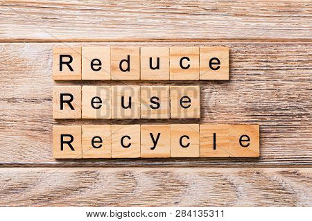 Reduce, Reuse And Recycle Word Written On Wood Block. Reduce, Reuse And Recycle Text On Wooden Table